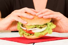 Black dressed woman holding a hamburger. Woman holding home made hamburger Royalty Free Stock Images