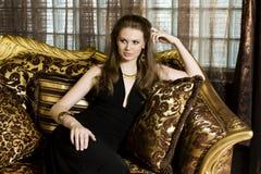 Black dressed woman sit on a gold sofa. Black dressed young woman sit on a gold sofa, looking away Stock Image