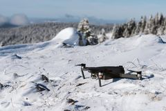 Black drone on a snowy slope ready to take off royalty free stock photos