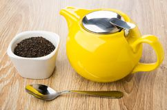 Black dry tea in glass bowl, yellow teapot and teaspoon. On wooden table Stock Photos