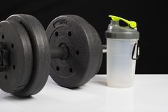 Black dumbbell, whey protein, on black and white backgrounds. Fitness royalty free stock photography