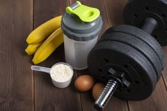 Black dumbbell, whey protein, eggs, ban on the wooden floor. View from above royalty free stock photos