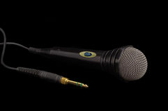 Black dynamic microphone and connector on a dark background. Dynamic microphone in black plastic housing with windscreen in wire mesh  and its phone connector on Stock Photos
