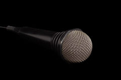 Black dynamic microphone on a dark background. Dynamic microphone in black plastic housing with windscreen in wire mesh on a dark background Stock Image