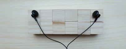 Black earphones over block. Black earphones over wooden board Stock Photos