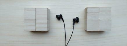 Black earphones. Over wooden board Stock Photo
