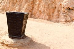 A black eco ooden large wicker basket for garbage, a trash can on a sandy beach in a tropical desert resort against the backdrop o. F a rock and a stone wall Stock Image
