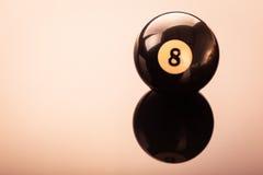 Black eight ball. A pool black eight ball shot over a dark reflective surface Stock Photos
