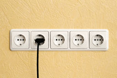 Black electric cable plugged in a white power socket Stock Image