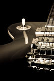 Black Electric Guitar. Isolated on black.Black and white photo with slight sepia toning Stock Photo