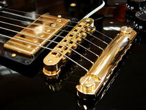 Black electric guitar. With gold strings Royalty Free Stock Photos