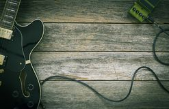 Black electric guitar, effect pedal on a rustic wood. En background, green tint, retro look Stock Photography