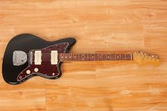 Black electric guitar, studio shoot. Red tortoise shell pickguard, alder body, maple neck, two single coil.  stock photography