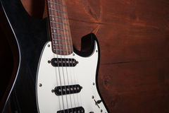 Black electric guitar. On the wooden background Royalty Free Stock Photos