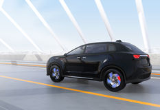 Black electric SUV driving on arc bridge Royalty Free Stock Photography