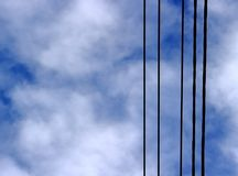 Black electric wires on a background of a cloudy blue sky royalty free stock photos