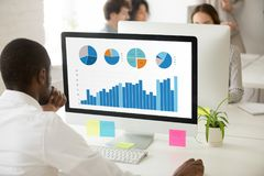 Black employee analyzing graphic data preparing statistical repo. African businessman analyzing graphic data charts graphs of marketing sales project performance stock image