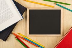 Black, empty, blank chalkboard with colored pencils and books on brown wooden desk flat lay from above royalty free stock image