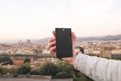 Black empty card in the hands of her husband against the background of Florence, Italy stock photo