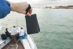 Empty card in the hands of her husband at the background of the sea and the nose of a tourist ship on which people are stock photos
