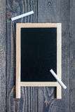 Black empty chalkboard for copy space with pieces of chalk Royalty Free Stock Photo