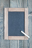Black empty chalkboard on wooden table for copy space, top view Stock Images