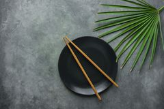 Black Empty Plate with Brown Bamboo Chopsticks Pal Tree Leaf on Dark Grey Stone Background. Asian Thai Chinese Cuisine Concept. Menu Poster Recipe Template Royalty Free Stock Photo