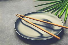 Black Empty Plate with Brown Bamboo Chopsticks Palm Tree Leaf on Dark Grey Concrete Stone Background. Asian Thai Chinese Cuisine. Concept. Menu Poster Recipe Stock Photo