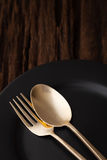 Black empty plate fork spoon on wooden table background Royalty Free Stock Photo