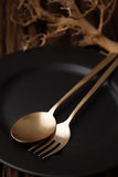 Black empty plate fork spoon on wooden table background Royalty Free Stock Images