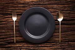 Black empty plate fork spoon on wooden table background Stock Photo
