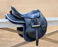 Black English saddle hanging on fence near stables. Royalty Free Stock Image