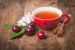Black english tea in red cup with cherry. On wooden background Stock Photo