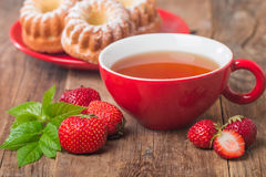 Black english tea in red cup with strawberry Stock Image