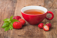 Black english tea in red cup with strawberry Royalty Free Stock Images