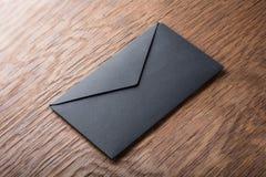 Black envelope on  wooden table Stock Photos