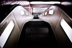 Black Escalator Near Red Wall Tiles Royalty Free Stock Photos