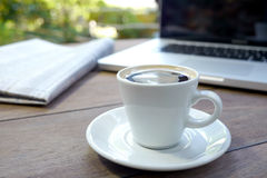 Black espresso cup of coffee with newspaper and computer Royalty Free Stock Photos