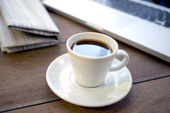 Black espresso cup of coffee with newspaper and computer Royalty Free Stock Photo