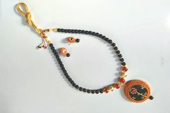 Black ethnic necklace with pendant of beads. Golden string and black beads with orange pendant Royalty Free Stock Image