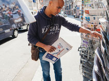 Black ethnicity man buying newspaper reporting handover ceremony. PARIS, FRANCE - MAY 15, 2017: Black ethnicity man buys international newspaper reporting Royalty Free Stock Image