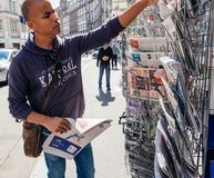 Black ethnicity man buying newspaper reporting handover ceremony. PARIS, FRANCE - MAY 15, 2017: Black ethnicity man buys international newspaper reporting Stock Photo