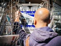 Black ethnicity man buys newspaper reporting handover ceremony p. PARIS, FRANCE - MAY 15, 2017: Black ethnicity man buying Le monde newspaper reporting handover Royalty Free Stock Photos