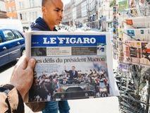 Black ethnicity man buys press reporting handover ceremony presi. PARIS, FRANCE - MAY 15, 2017: Le Figaro newspaper with black ethnicity man buying newspaper royalty free stock image