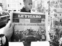 Black ethnicity man buys press reporting handover ceremony presi. PARIS, FRANCE - MAY 15, 2017: Le Figaro newspaper with black ethnicity man buying newspaper stock photos