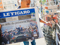 Black ethnicity man buys press reporting handover ceremony presi. PARIS, FRANCE - MAY 15, 2017: Le Figaro newspaper with black ethnicity man buying newspaper Stock Images
