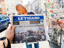 Black ethnicity man buys press reporting handover ceremony presi. PARIS, FRANCE - MAY 15, 2017: Le Figaro newspaper with black ethnicity man buying newspaper Stock Photography
