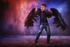 Free Black Evil Angel On A Dark Background With Colored Lighting. The Concept Of War Between Good And Evil. Boy With Angel Wings During Stock Image - 175257271