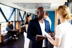 Black executive talking to white female colleague stock photos
