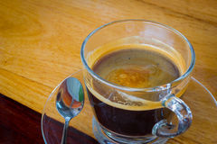 Black expresso coffee in small glass cup on wooden table with te Royalty Free Stock Image